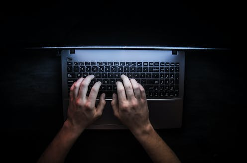 Hands on a keyboard with a dark background