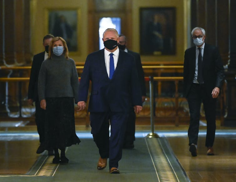 Doug Ford, wearing a mask, walks into a news conference at Queen's Park.
