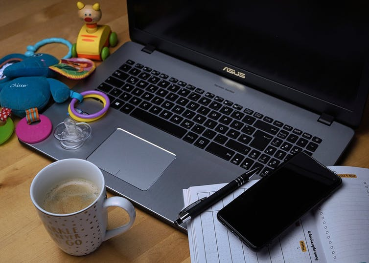 A laptop is seen baby paraphernalia nearby, including a pacifier and teething ring.