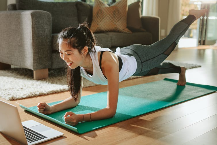 A woman doing planks with a leg outstretched and looking at laptop.