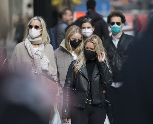 People in winter clothing wearing face masks walking down the street.