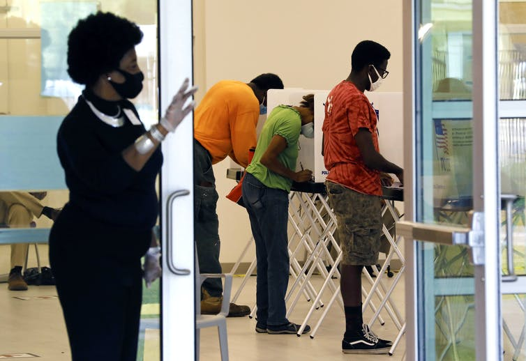 Woman stands by door of room where people are voting using machines.