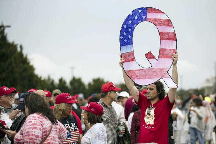 A man in a red T-shirt holds up a letter Q illustrated with stars and stripes.