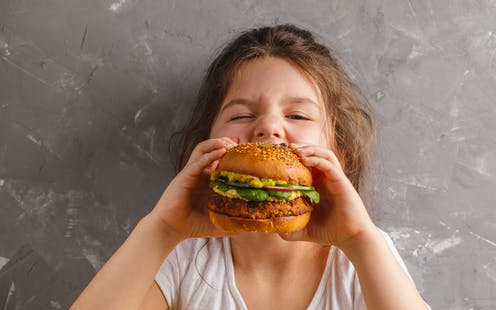 A young girl biting into a veggie burger.