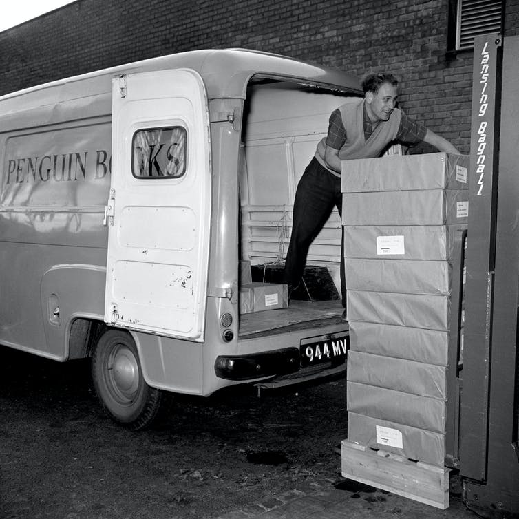 Men load a van with books, 1960.