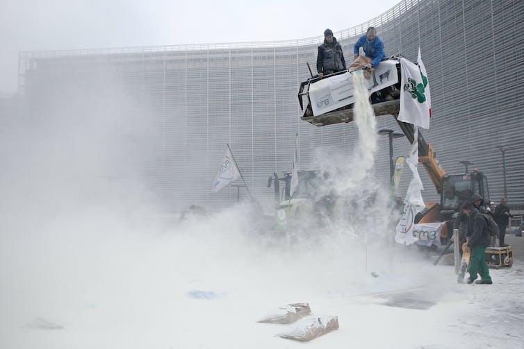Protesting farmers dump milk powder from a platform outside the EU Parliament.