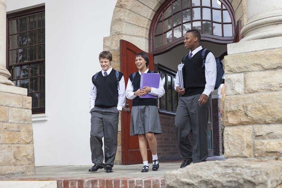 Three pupils wearing school uniform in front of a school building.