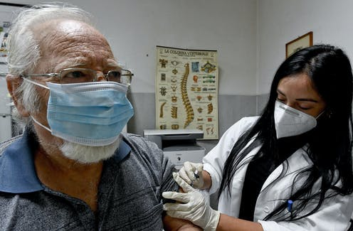 A medic administers a flu vaccine to an elderly patient