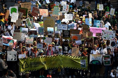 Ratusan aktivis lingkungan membawa slogan protes.