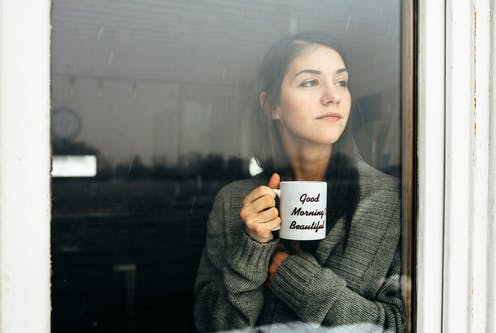 A woman holding a mug saying 'good morning beauitful' looks out of a window.