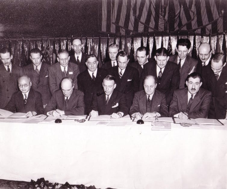 A black-and-white photograph of men standing around a table.