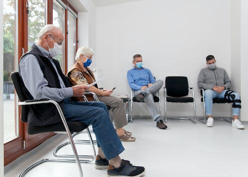 Cuatro personas con mascarilla en una sala de espera.