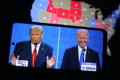 Debate electoral entre Trump y Biden visto en un teléfono móvil, con mapa de Estados Unidos detrás.