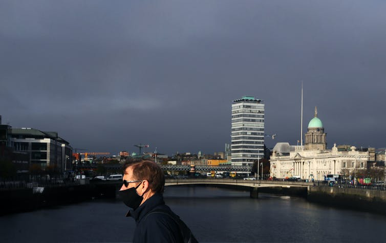 A man wearing a mask walks across a bridge in Dublin.