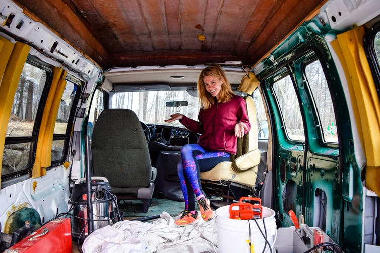 A woman sits smiling in the back of her van.