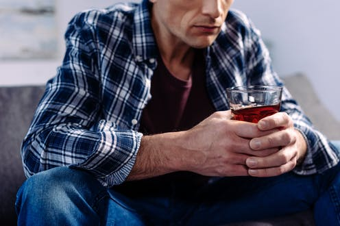 A man clutching a glass of alcohol.