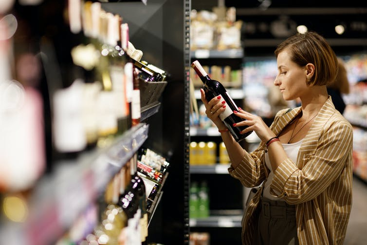 A woman looks at a bottle of wine in a store.