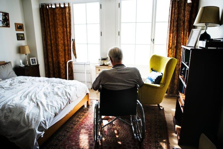 Homme plus âgé en fauteuil roulant dans la chambre.