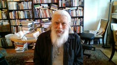 An older man with a huge white beard sits looking at camera, behind him a study and shelves of books.