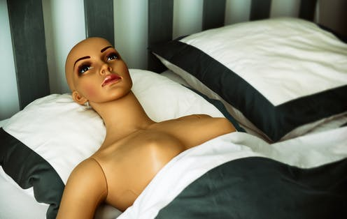 Naked plastic woman lying in bed.