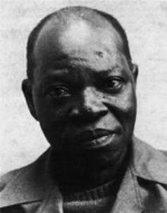 In black and white, a balding dark-skinned man looks frankly and openly at the camera.