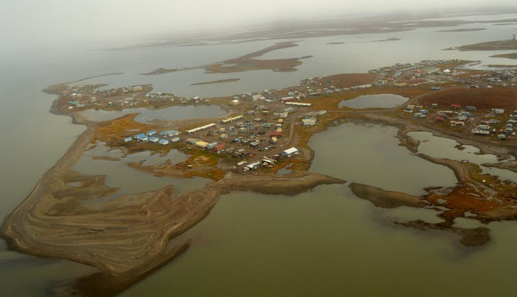 Aerial view of a low-lying coastal town built on permafrost.