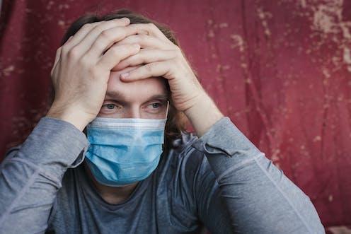 Un hombre con mascarilla y cara de cansancio se sujeta la cabeza con las manos.