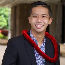 Headshot of Tam wearing a red lei