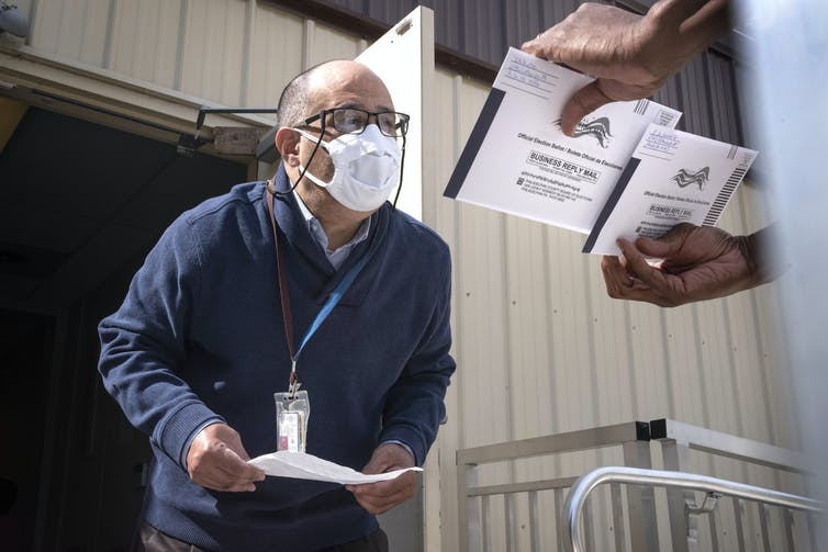 A man in a mask peers at election documents