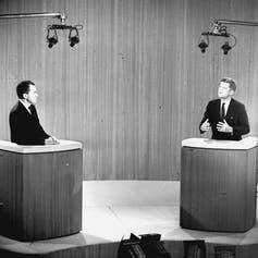 Richard Nixon and John F. Kennedy are seen debating in television studio.