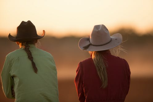 Two farmers facing away, looking at the sunset