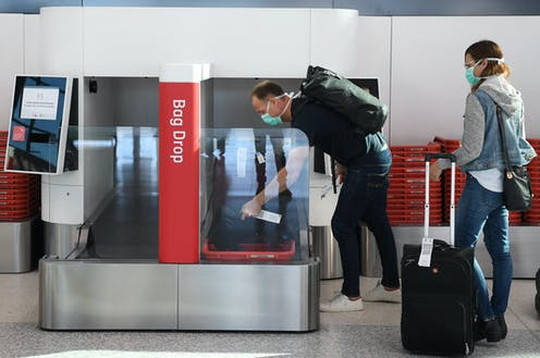 A man loads luggage onto a bag drop at Sydney airport.