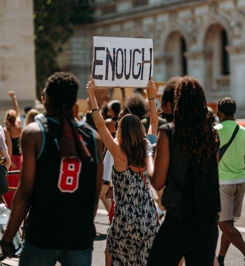 Protestors. A sign reads 'enough'.