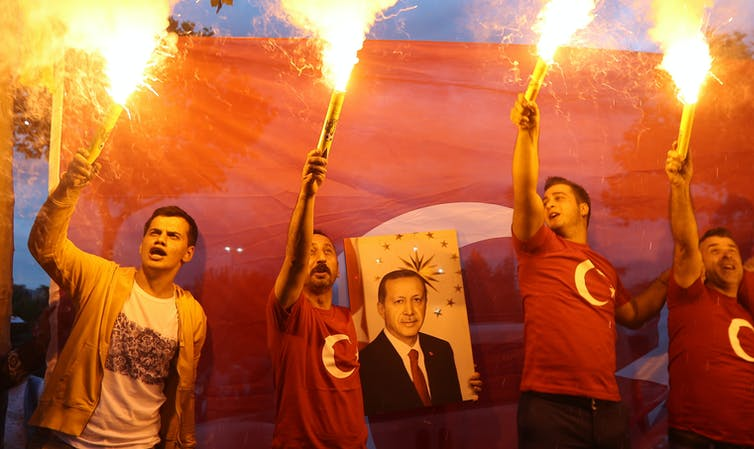 Men holding torches hold poster of Turkish president Recip Tayyip Erdoğan