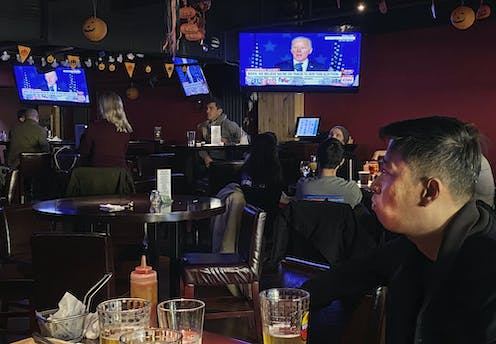 Customers watch the election might coverage at a bar in Beijing.