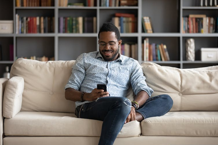Man sitting on couch looking at his phone.