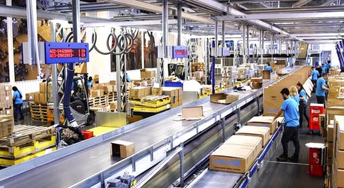People working in a warehouse where boxes roll along a conveyor belt.