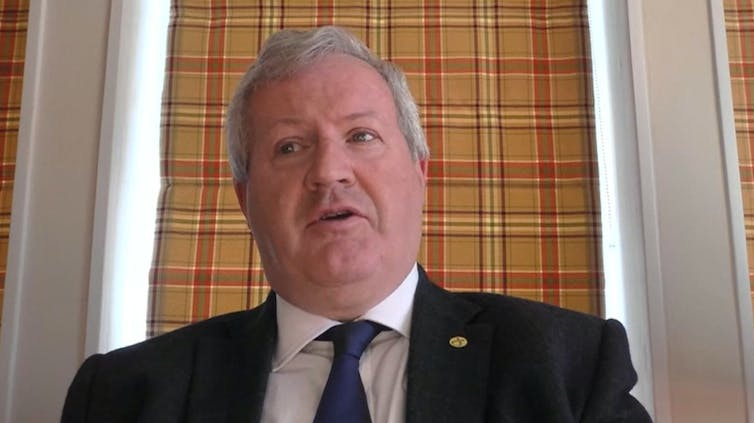 SNP MP Ian Blackford sits in front of his tartan curtain.