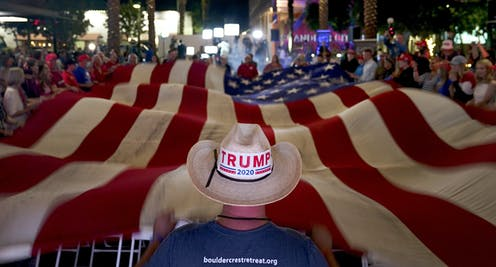 A person wearing a cowboy hat with a Trump sticker standing at the end of a large American flat.