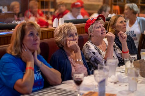 Four women sitting at a table watch the presidential election returns.