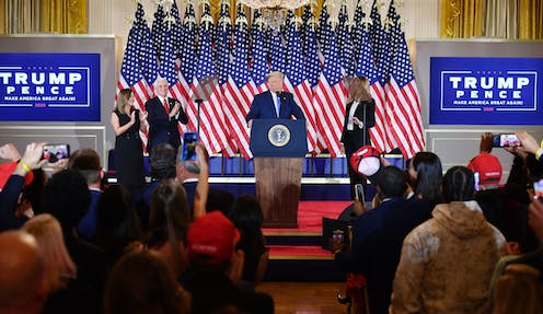 Trump flanked by his wife and vice president speaks in front of an array of American flags at the White House