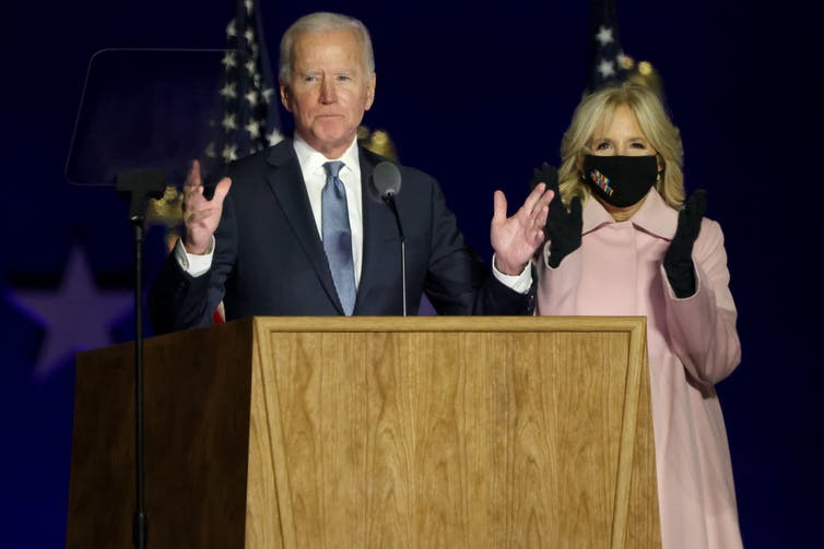 Biden speaking at a lectern next to his wife, who wears a face mask
