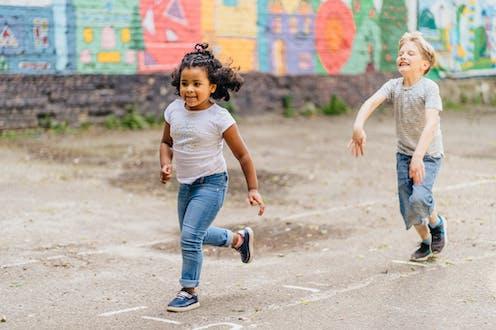 Two children running on street