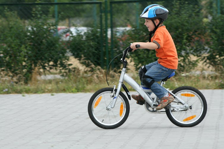 Boy cycling on paved street
