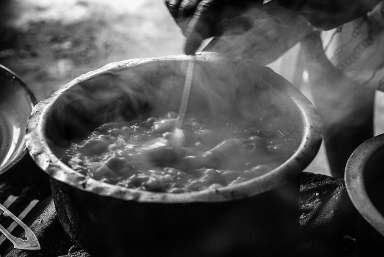 A hand stirs a steaming and battered metal pot with a spoon. The contents resemble a stew.