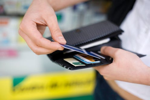 man's hand pulls out card from wallet
