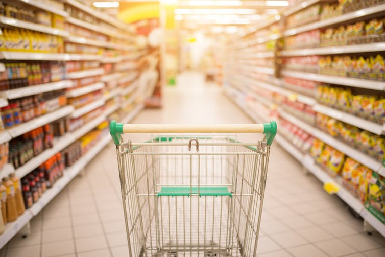Empty shopping trolley in supermarket aisle.