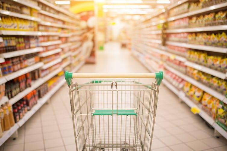 Empty shopping trolley in supermarket aisle.