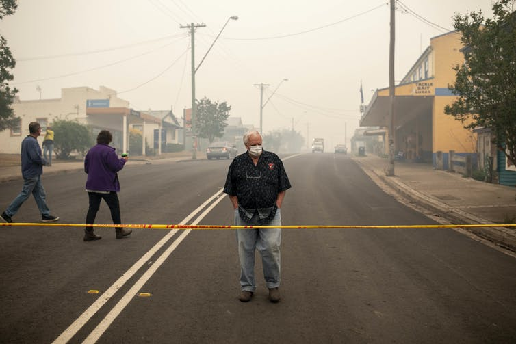 A man standing behind a cordoned off area with thick smoke behind him, in Cobargo, NSW.