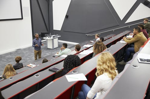 Students listen to lecturer in a half-empty lecture theatre